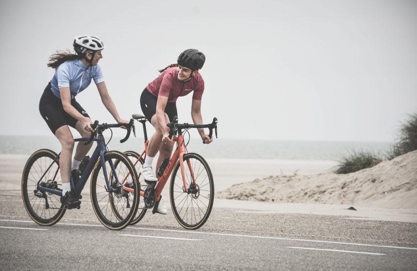 Dos mujeres haciendo ejercicio aeróbico en bicicleta por carretera